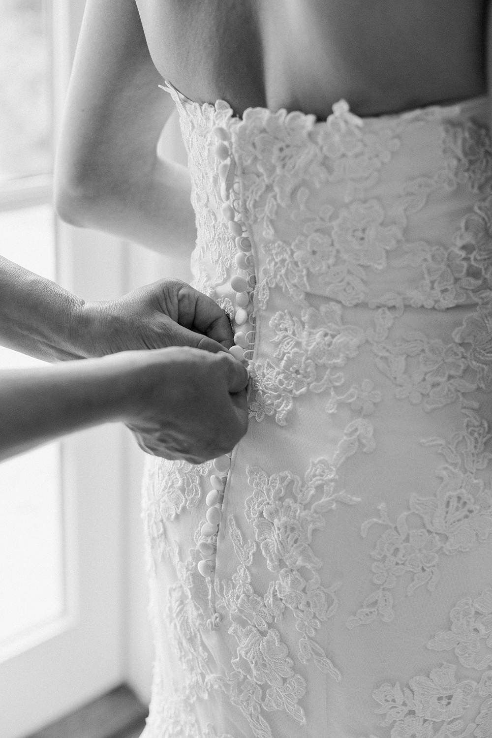 The brides' sister helping put on her wedding dress.