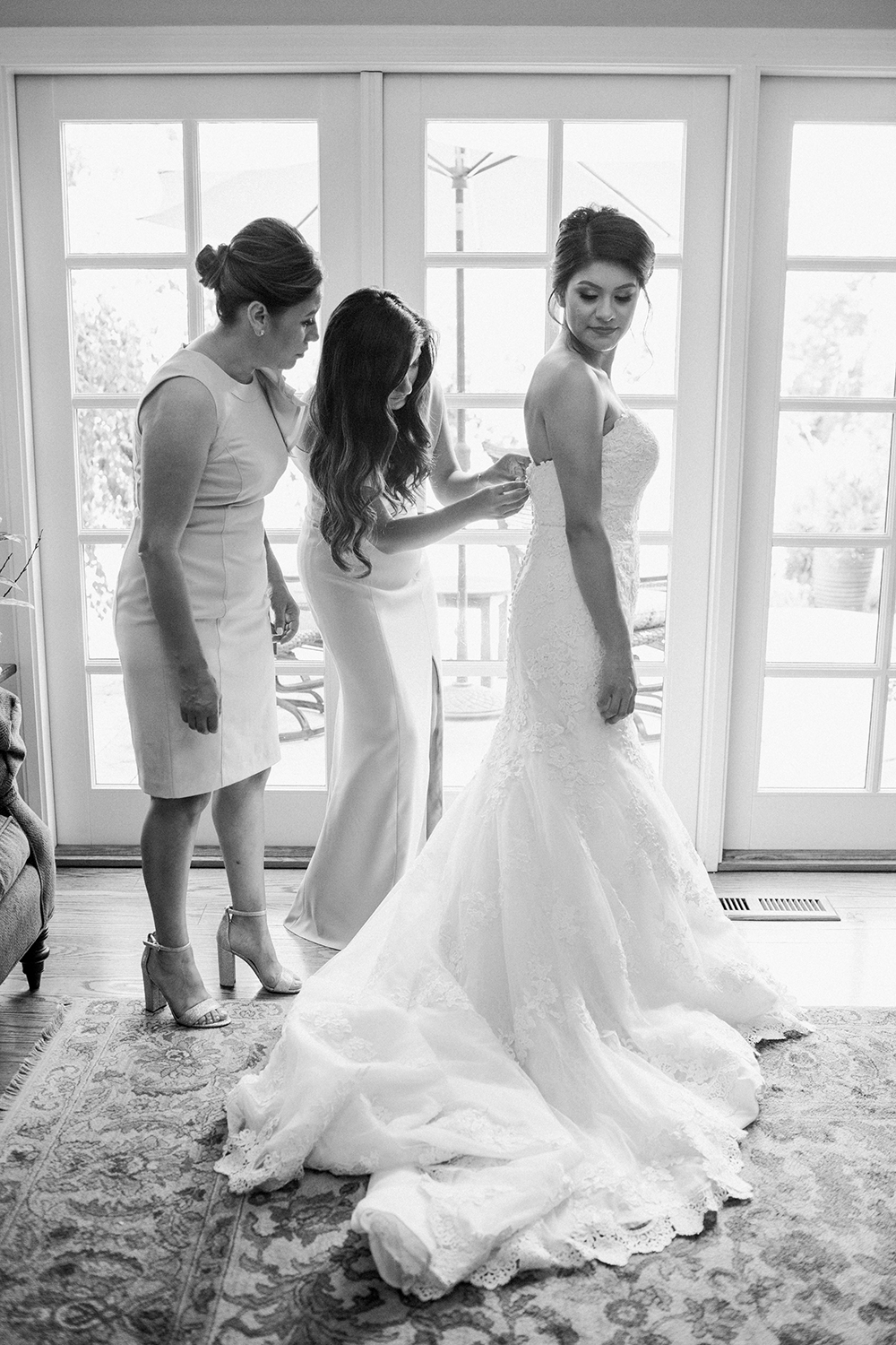 Sister and mother helping the bride with her wedding dress before heading to Mission Santa Clara.
