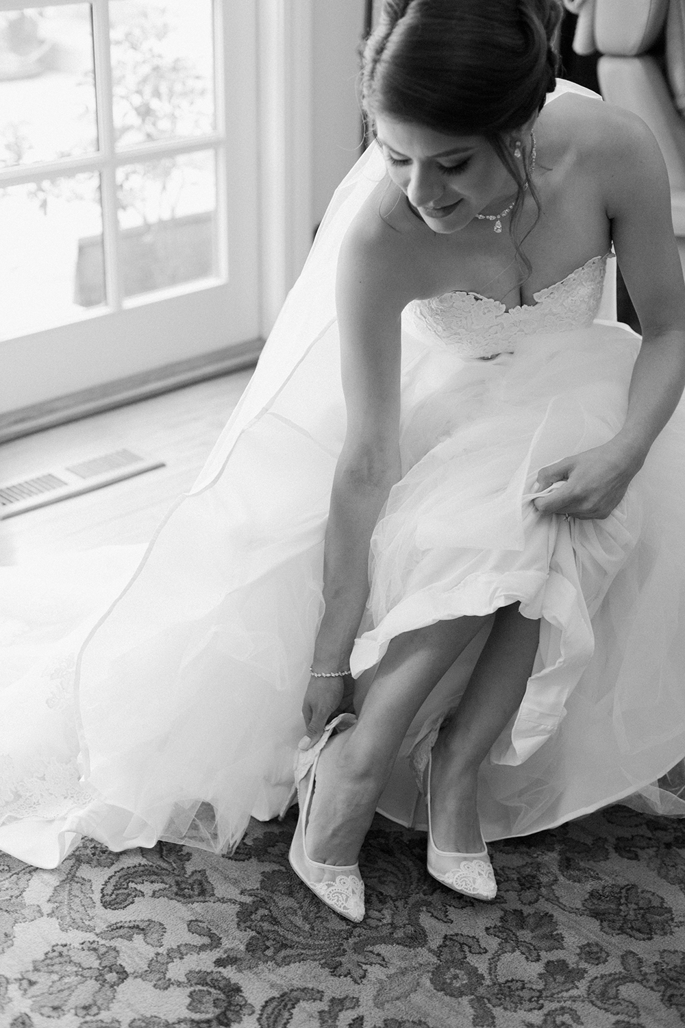 A bride sitting down to put on her wedding shoes.