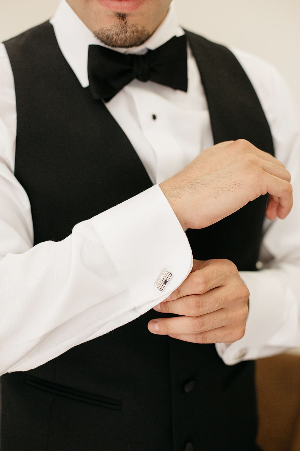 Groom getting ready and adjusting his cufflinks.