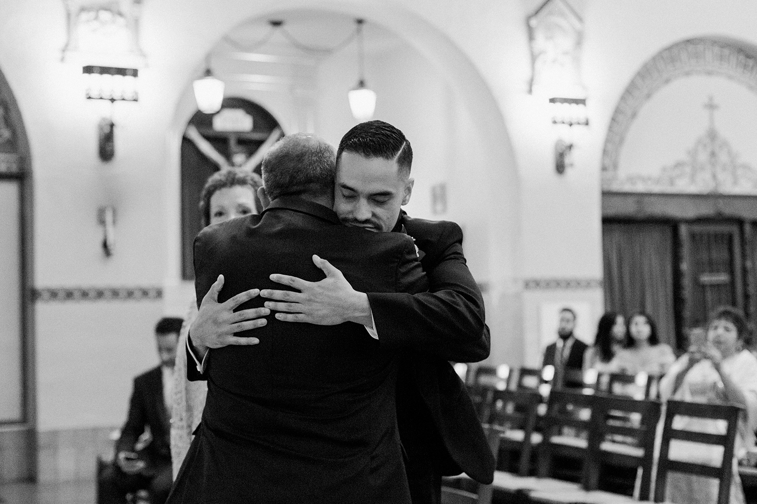 Groom hugging his father during his wedding ceremony in Mission Santa Clara de Asís.