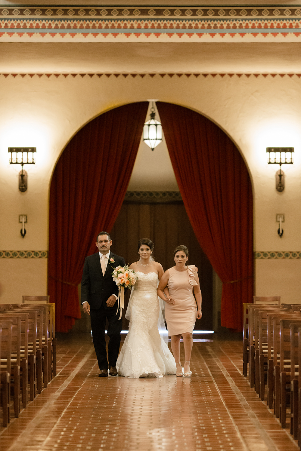 Bride walking down the aisle with both parents during her wedding in Mission Santa Clara de Asís.