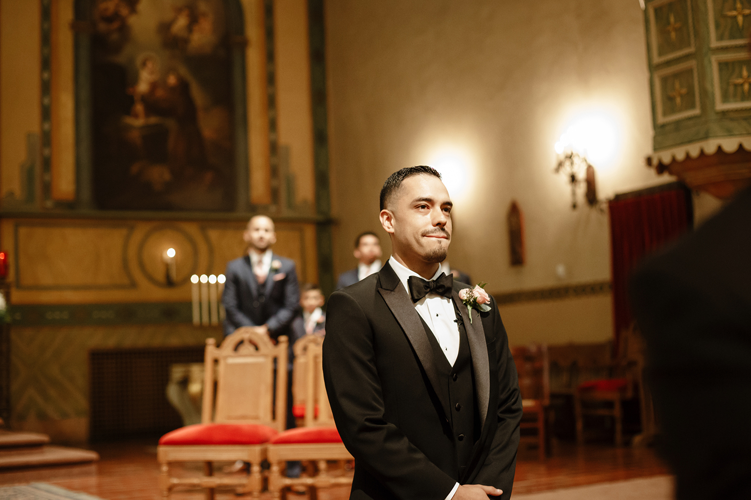 Groom waiting at the alter for his bride to walk down the aisle during their wedding in Mission Santa Clara de Asís.