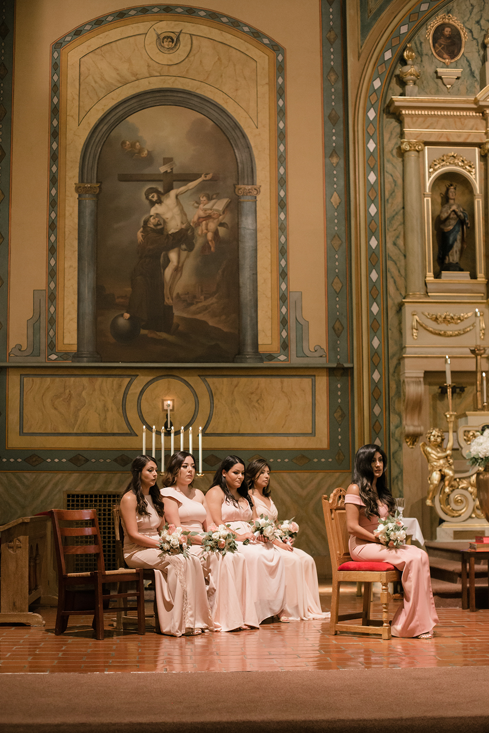 Group of bridesmaids sitting at the altar during wedding ceremony.