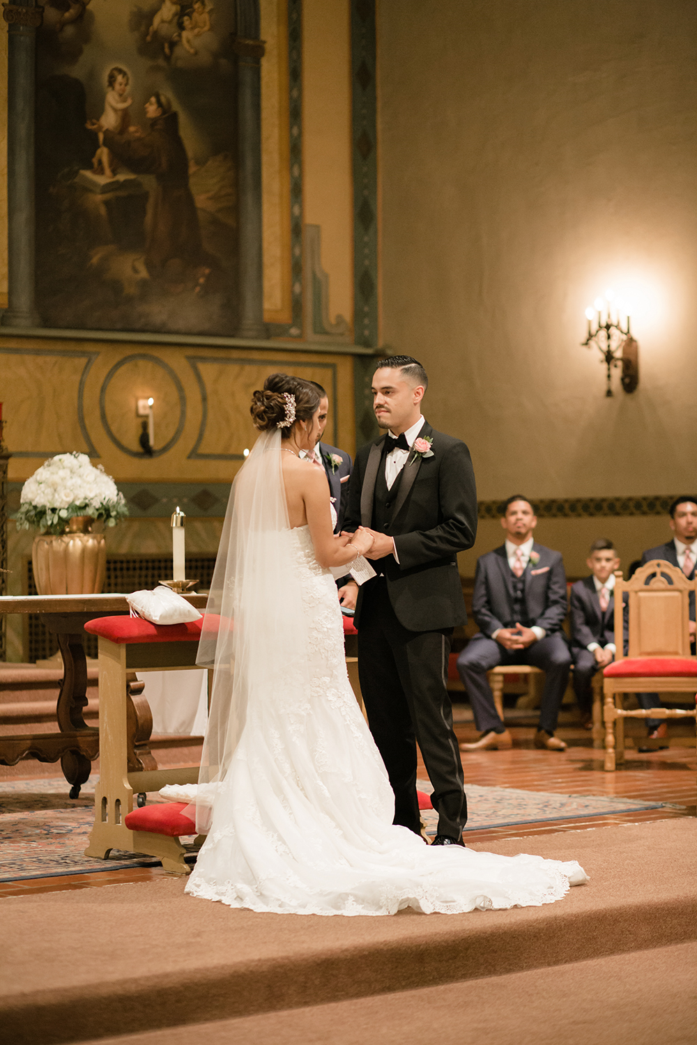 Bride and groom exchanging vows during their Mission Santa Clara de Asis wedding.