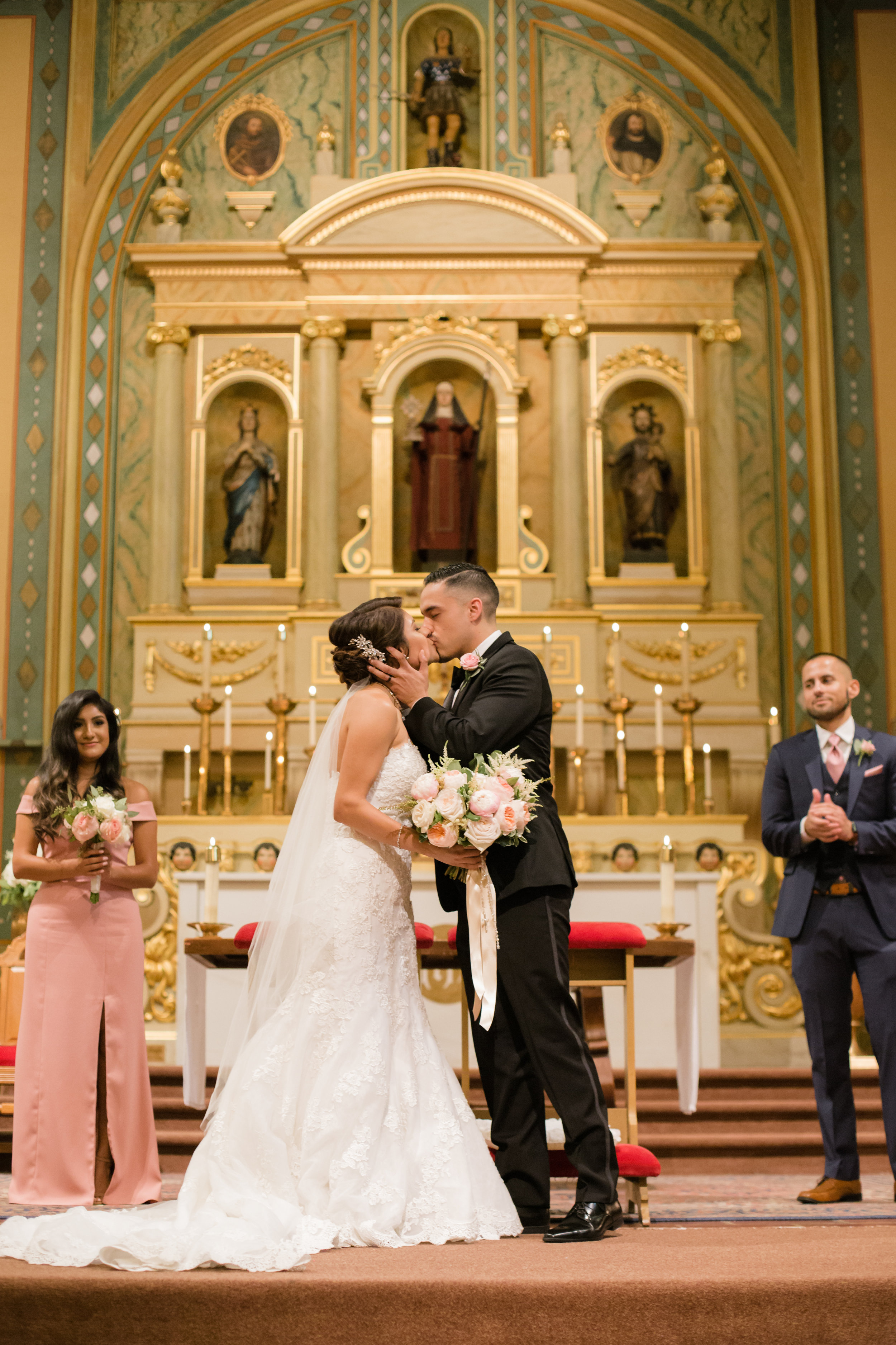 The first kiss during a wedding at Mission Santa Clara de Asís.