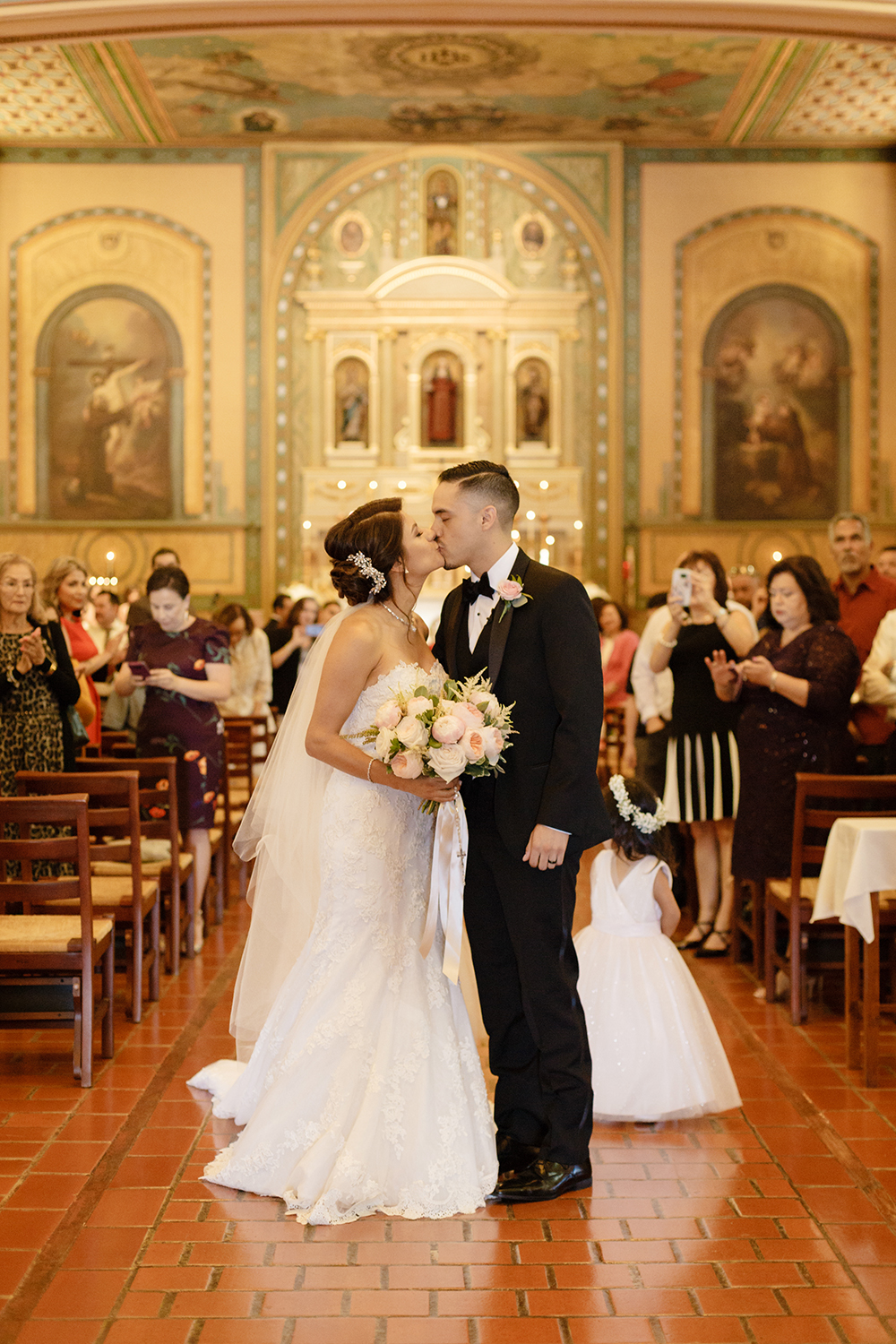 Bride and groom kissing on the church aisle as their guests watch. Mission Santa Clara de Asis wedding.