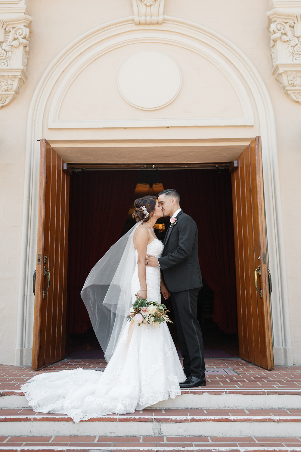 Bride and groom kissing outside the steps of Mission Santa Clara de Asís.