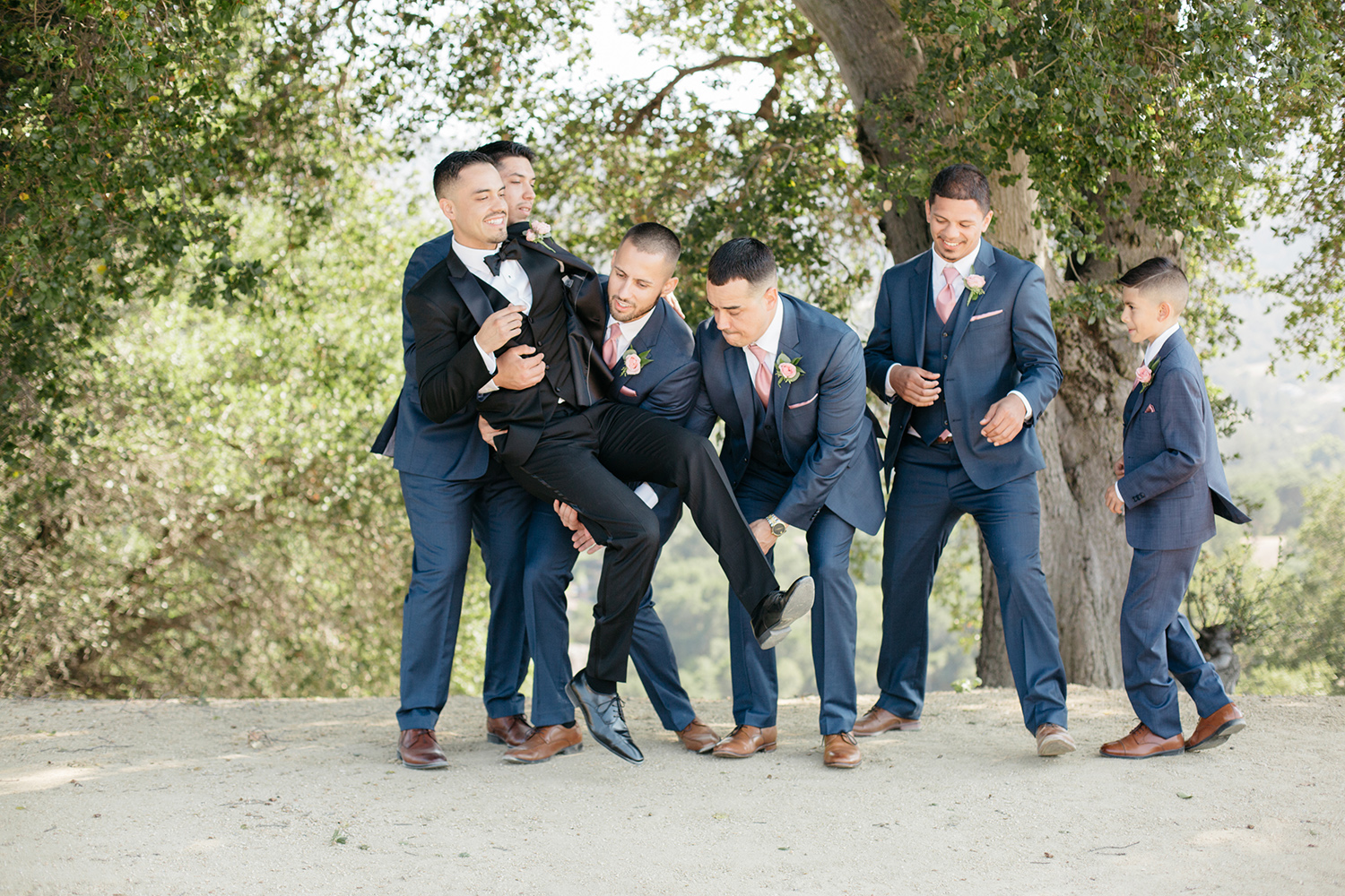 Groomsmen lifting up the groom for a fun pose.