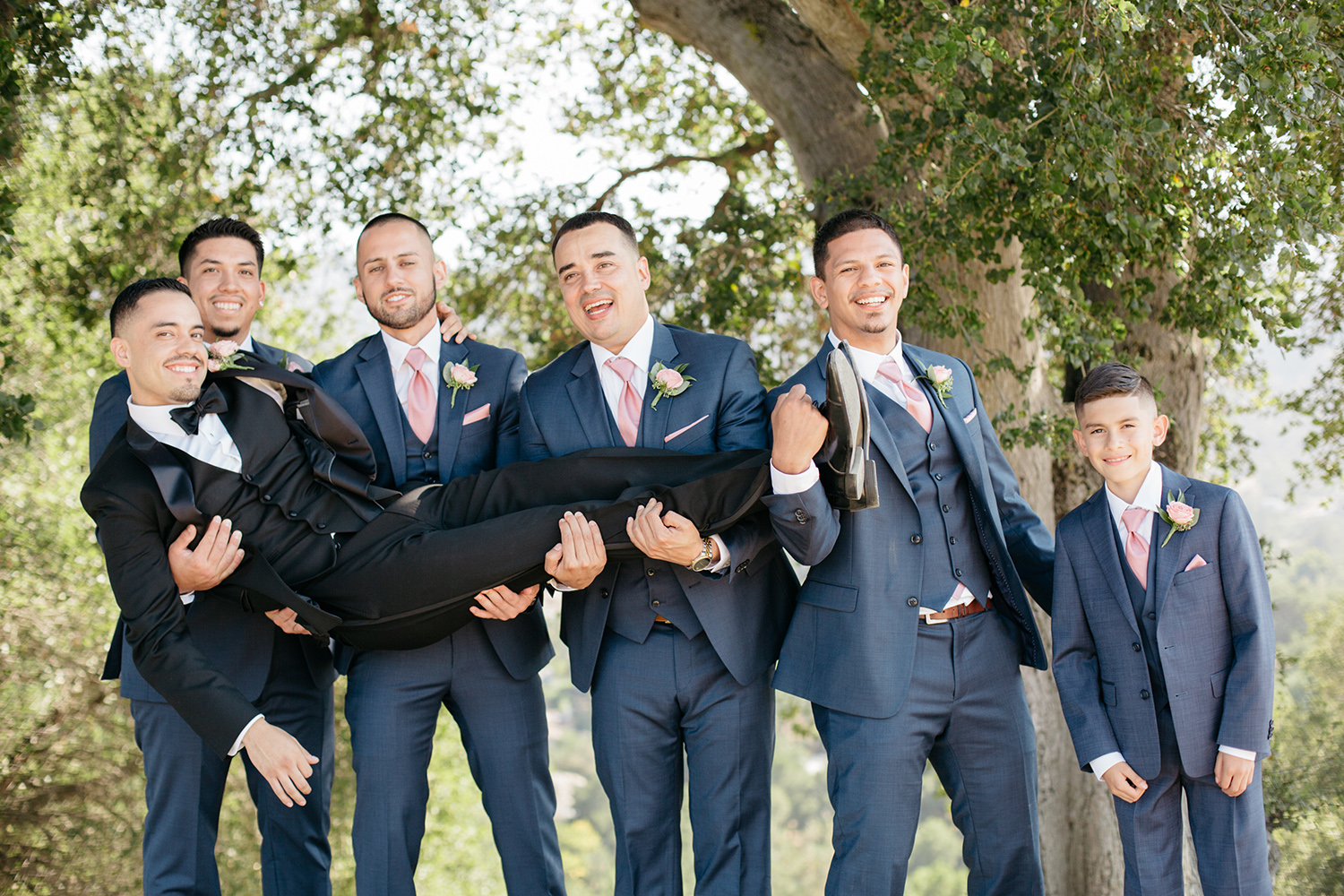 A group of groomsmen in blue suits holding a groom up.