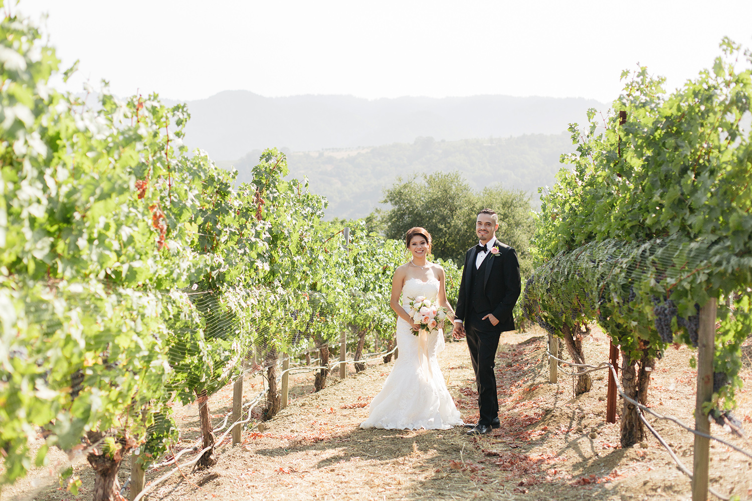 Bride and groom posing for a photo vineyards in Saratoga, California.