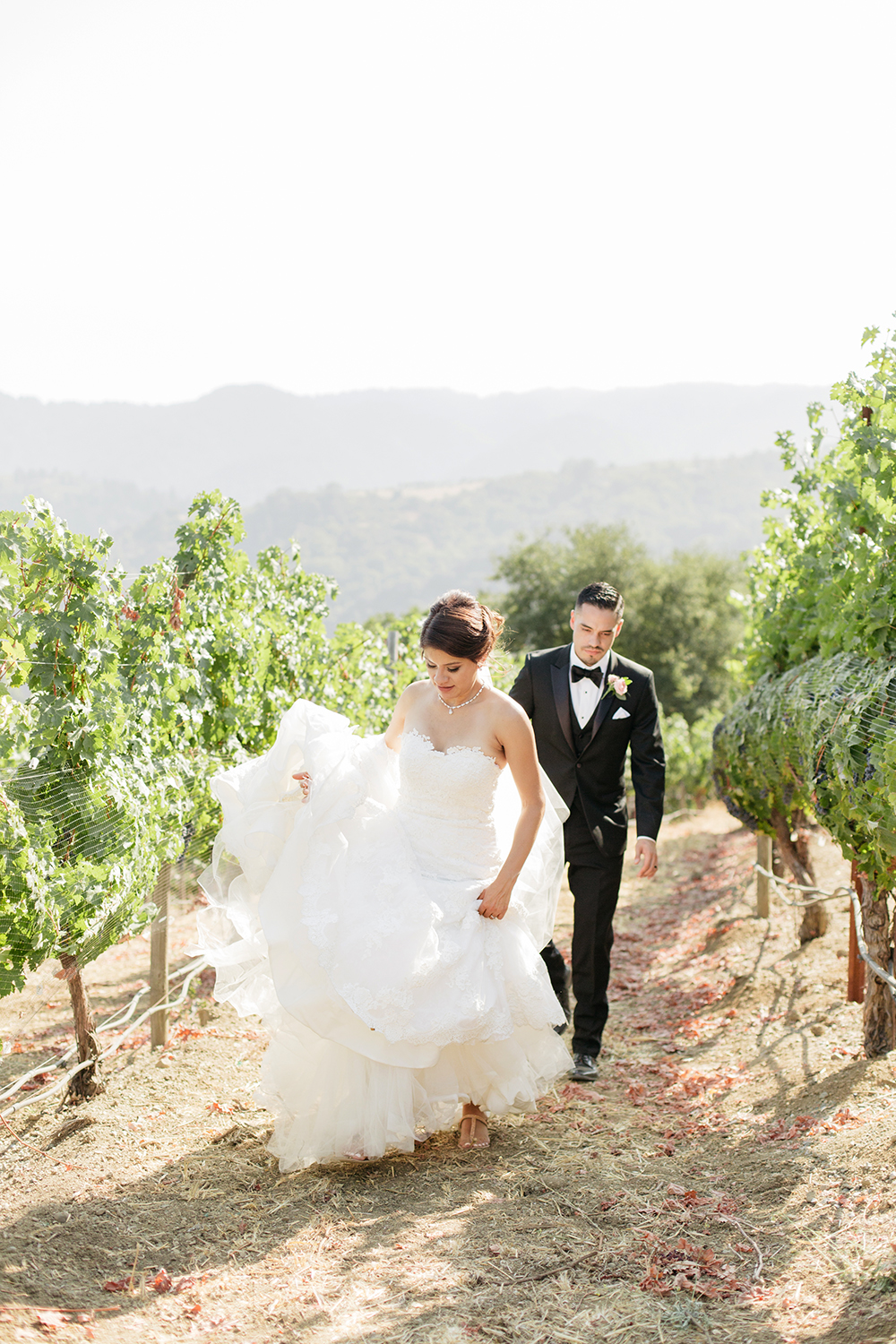 Bride and groom walking in a vineyard at their wedding in Saratoga, California.