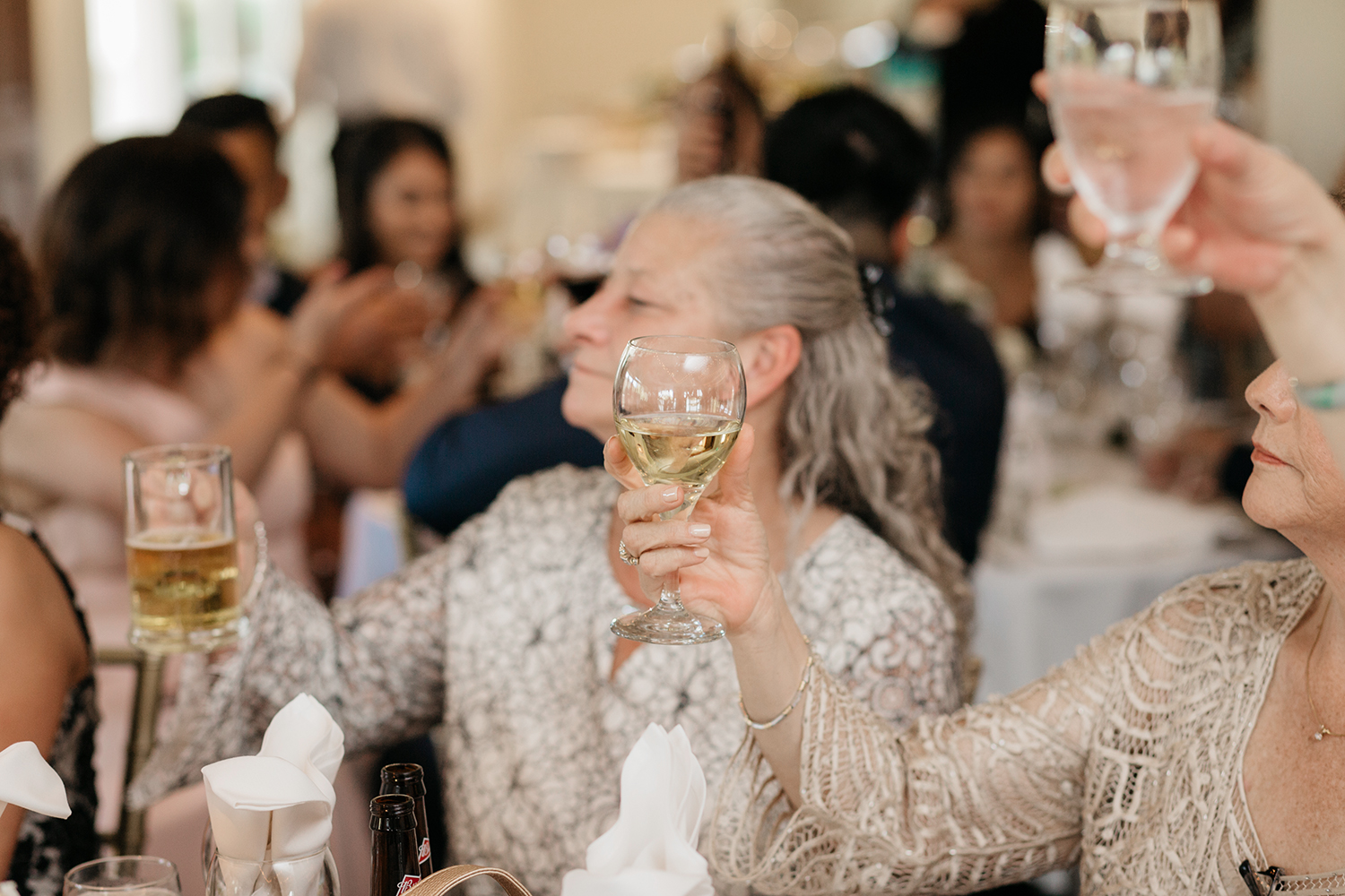 Guests lifting up wine glasses during a toast at a wedding in Saratoga Country Club.