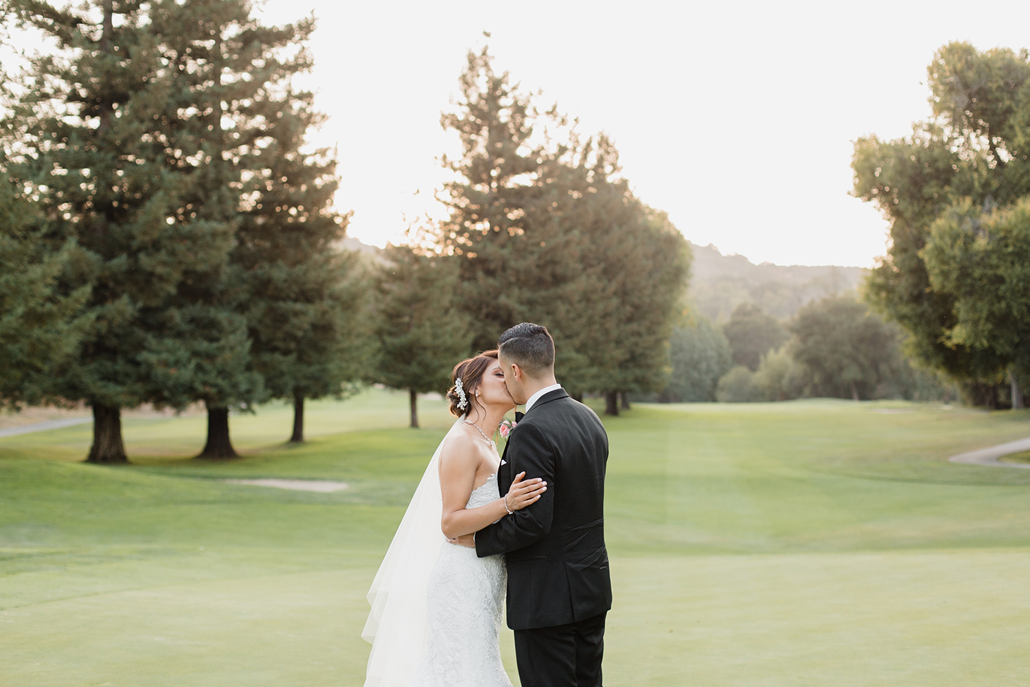 Bride and groom kissing during sunset at their wedding in Saratoga Country Club.