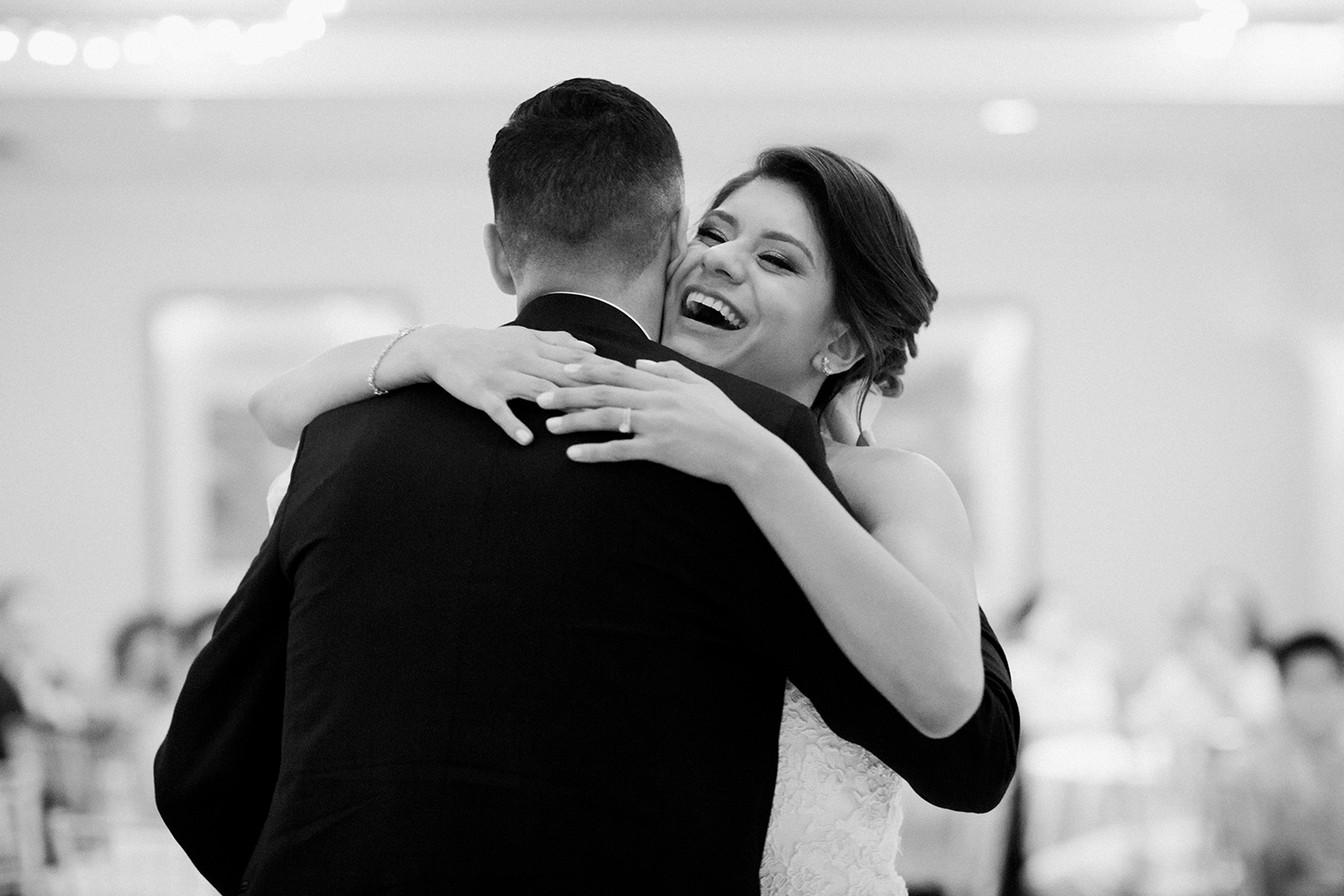 A candid fun moment of a bride hugging her groom during their romantic first dance.