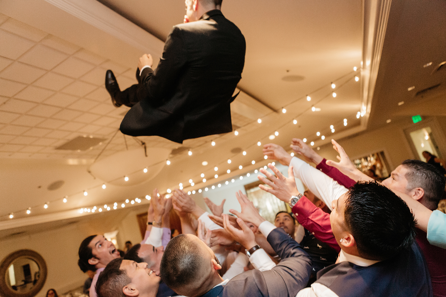 Groom being thrown up in the air by all his guests at his wedding in Saratoga Country Club.