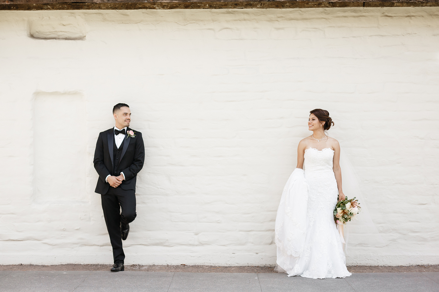Bride and groom standing by an adobe wall, looking at each other.