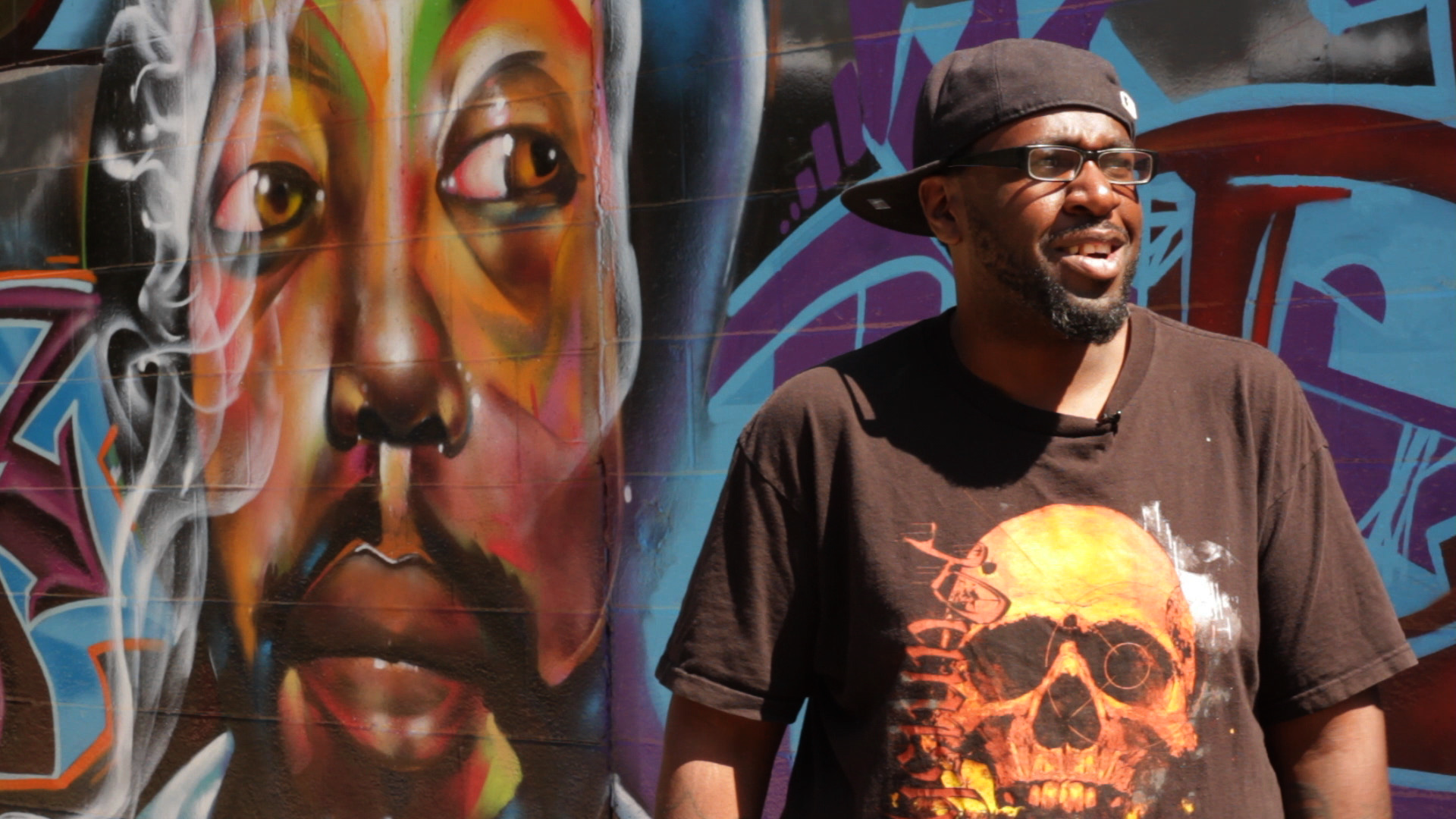 Will Condry, known as Kasso in the community, stands in front of a large mural he created as the driving force behind an event called New Jersey Fresh Jam, where artists from around the country gather for a hip hop jam and beautification project.