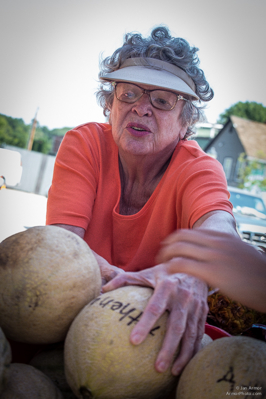 "A woman reachies for a squash at the Jonnycake Center's ""Farmers Market."" Growers and Super Markets from around the area donate fresh produce to help feed those in need."