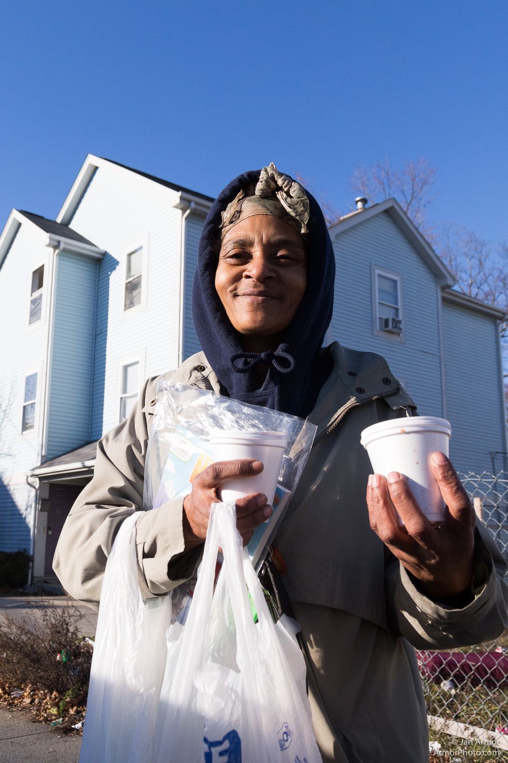 Debbie holds up a hot chocolate and some food for her children.