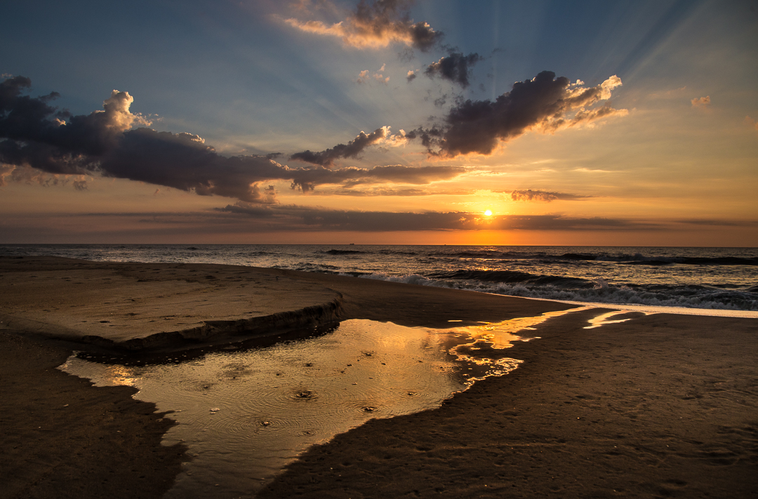 """24th Street Homecoming - The sunrise on Wednesday, September 14, 2016, was one of those once in a life time gifts the photo gods bestow on photographers. We had just come to Ship Bottom, NJ, for a short visit with my sister Vicki in the nursing home. I thought, feared, this may be the last time I would ever see her now that she is moving to her son's home in Frederica, Delaware, population 774. I hope it works out for her there, and in many respects this arrangement is far more sensible than living alone in our cold summer cottage on 24th Street. And it will cost less money than a nursing home.  I was up out of the lumpy bed room off the living room at 5:30 AM, the one we always thought of as Aunt and Uncle's bedroom. The same one that had so many memories for me in a wild and crazy youth """"down at the shore."""" Kathy slept. I looked out the door to the north and saw lovely puffy clouds hanging out in a dark sky. This sunrise had the promise of something special.  We lived just a few houses from the beach. I climbed the stairs at the top of the street and as I cleared the top of the dune I noticed a silent figure sitting ghost like on the bench. It was a woman, bundled up against the cold. She sat perfectly still, perhaps meditating to the sunrise to come. I made a few exposures with her silhouetted against the deep purple sky, ditched my sandals, and offered her a """"Good morning."""" Not a word came over my shoulder from her, no greeting, just a dark silence and sounds from the sea. I walked down the dunes to the shore. """"Good, not another reliving soul on the beach in either direction."""" It is always a joy to be so alone, especially here. This place felt so familiar, an echo from my youth. The cool sand felt very familiar between my toes.  The sky lightened but large clouds hung very still to the north. I could see the lights of a distant ship way out on the horizon. I waited and watched the incoming tide begin to wash away a little bank of sand. I left foot prints in the """