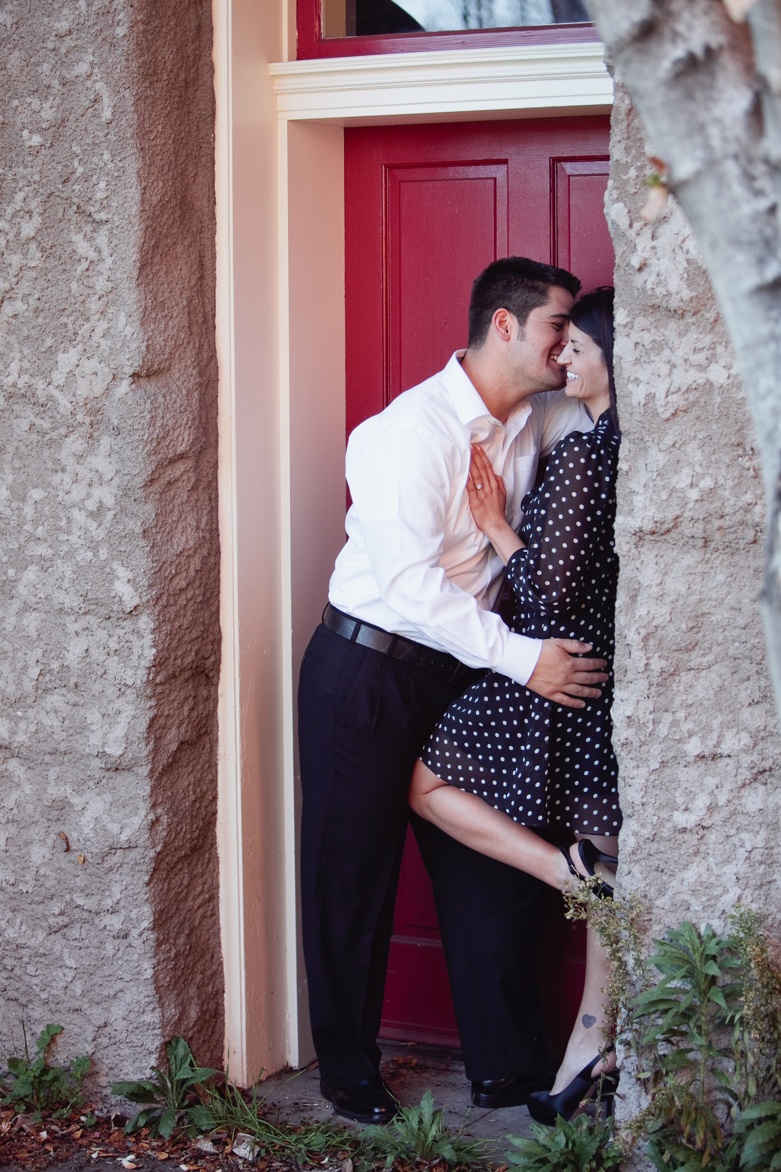 engaged couple in red doorway