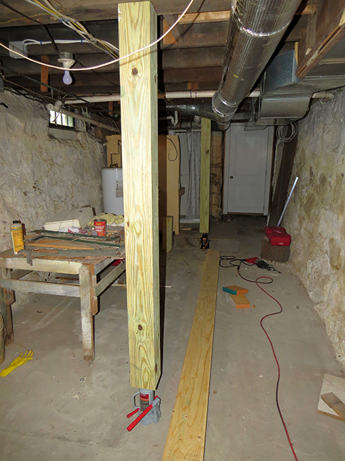 Kitchen floor being straightened in the basement with hydraulic jacks.