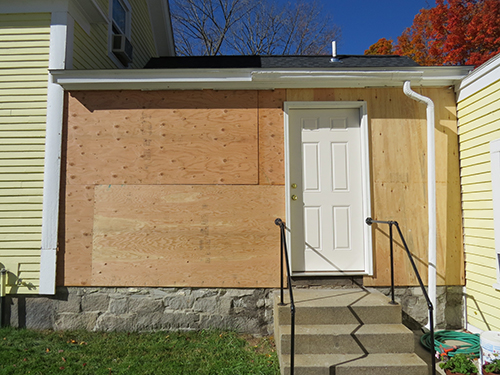 Porch from the outside with a temporary door and boarded up windows.