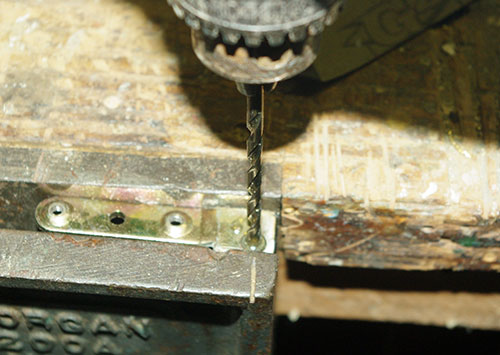 Step 2:  Drilling the old rivets out of the broken hinge.