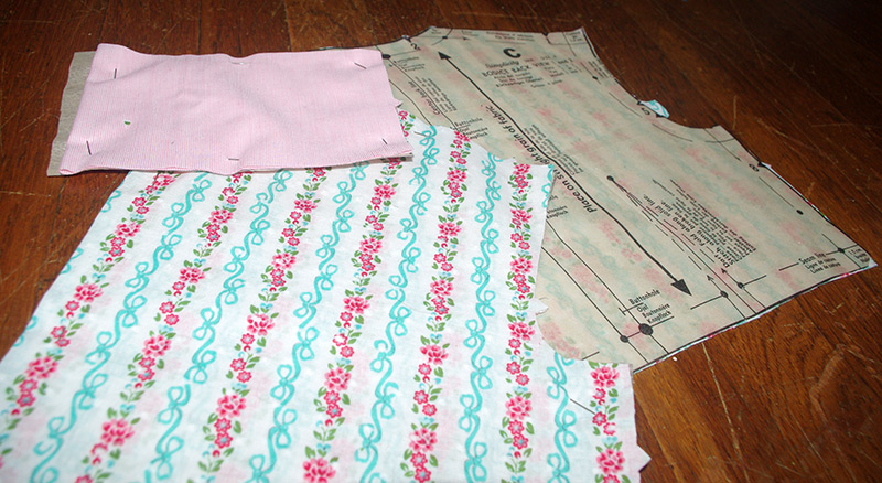 """Cutting out the pattern pieces. The pink fabric is vintage and the patterned is modern fabric by """"Gertie Fabrics""""."""