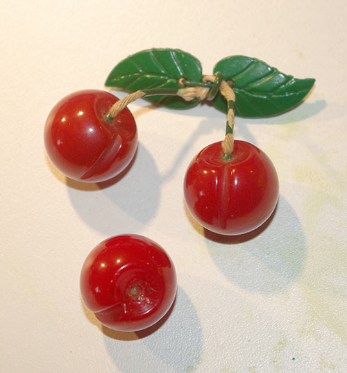 The spare cherry brooch I bought for parts, along with one of the cherries from the original necklace. The leaves are celluloid and I'll save those for a future project.