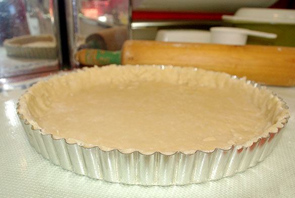 The tart pan lined with dough