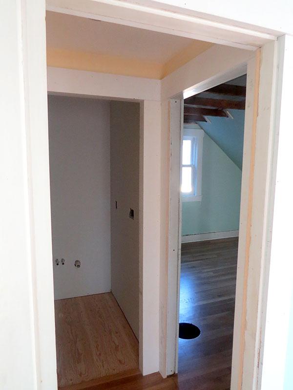 The door on the left was originally the door to the back bedroom but is now the bathroom door. The door on the right was added for the back bedroom.
