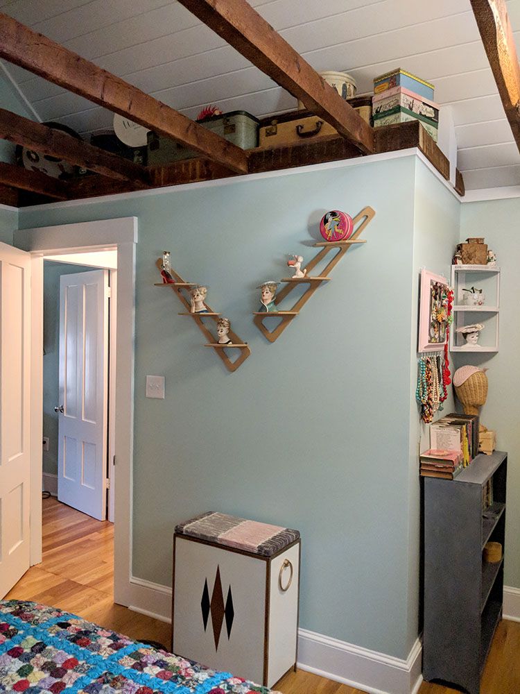 """The other side of this wall is where the bathroom is located. The """"roof"""" of the bathroom makes a great place to store and display vintage suitcases."""