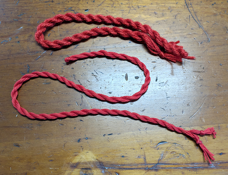 The top cord is made with yarn and the bottom cord with embroidery thread.