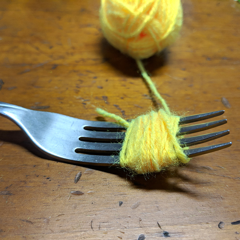 Making mini pompoms with a fork and some yarn