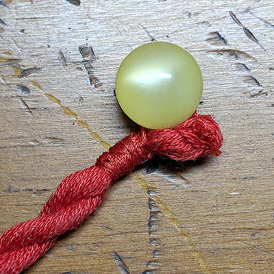 The knotted end of the cord with ball button attached.