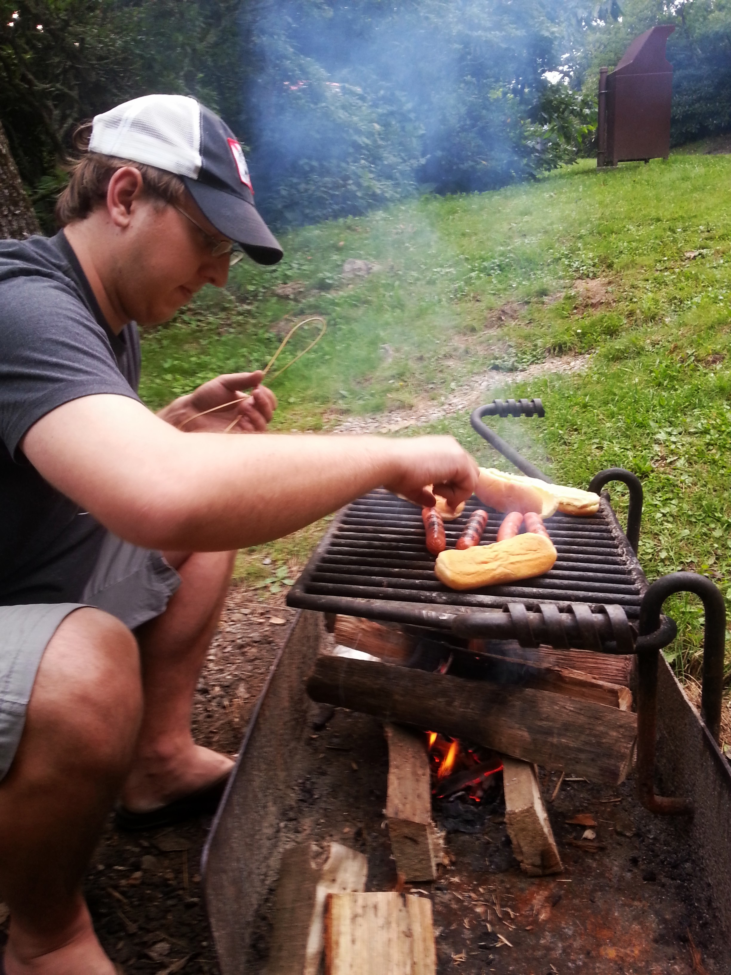 Despite the drizzling rain McCrae got just enough fire going to toast some hotdogs and buns.