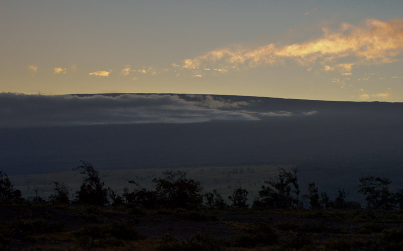 Mauna Loa. It may not look like much except for a slight rise in the horizon against a sunset, but that's only because the mountain is SO BIG. That whole thing is mountain, and it just keeps going.