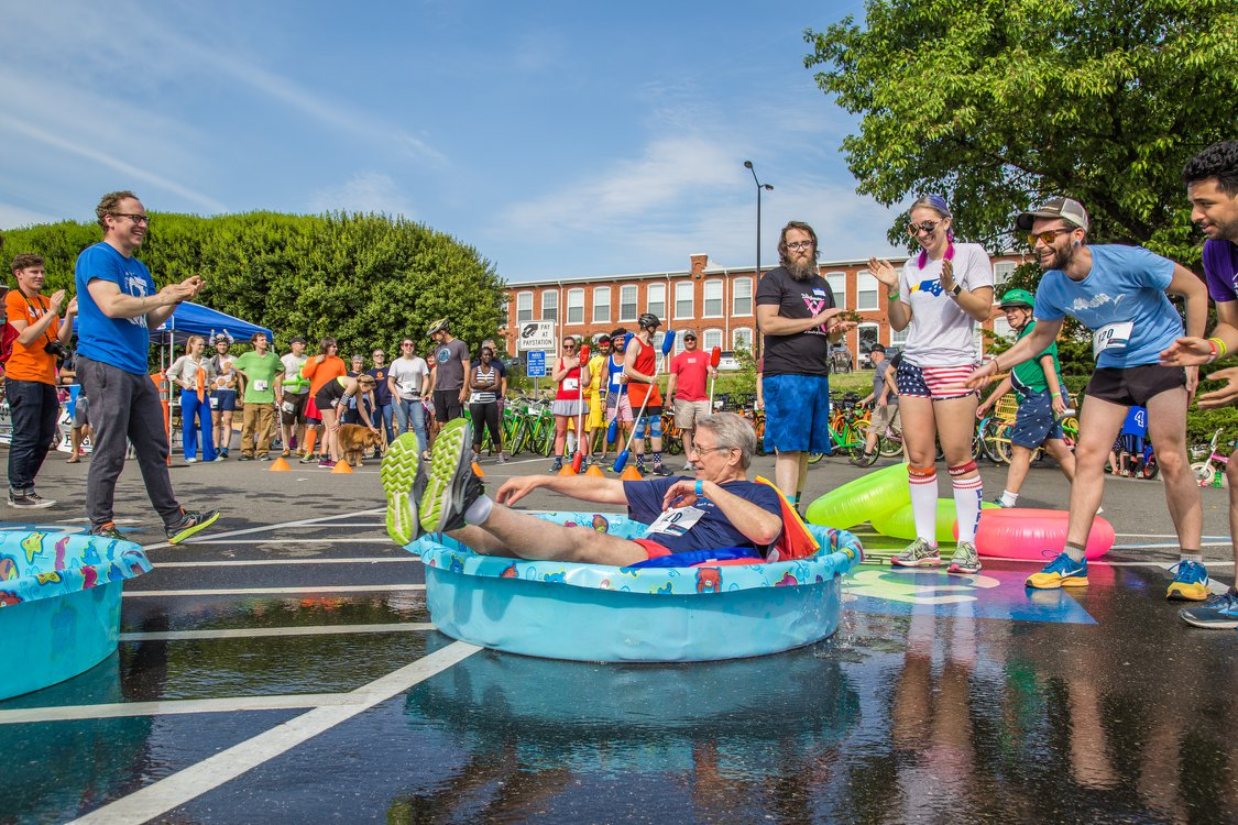 """Mayor of Durham Steve Schewel takes a turn in the kiddie pool for his team's """"swimming"""" leg.Photo courtesy of  Doughman"""