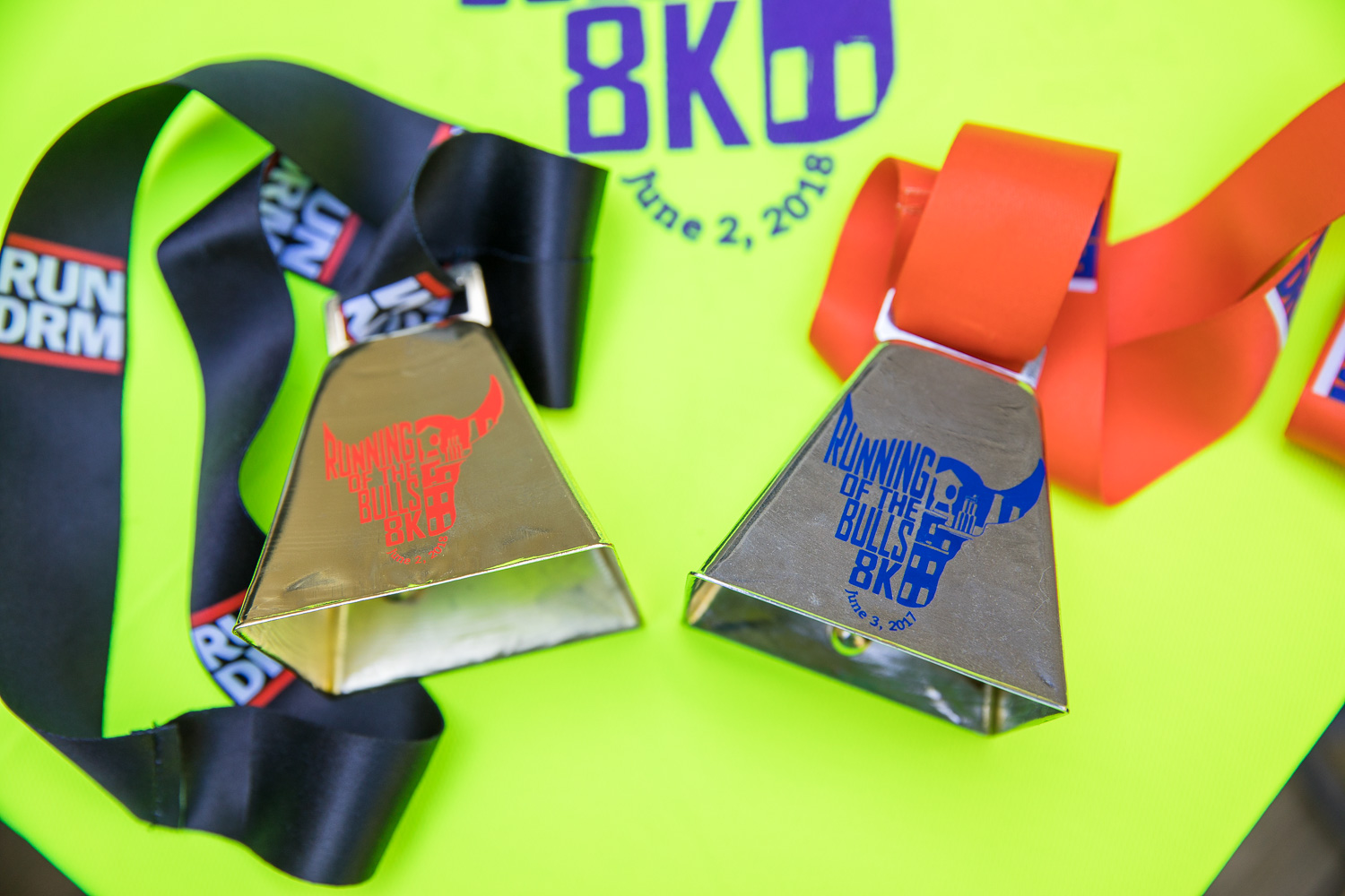 2018 (left) race medal was gold with black ribbon. 2017 (right) race medal was silver with orange ribbon. Both are cowbells!
