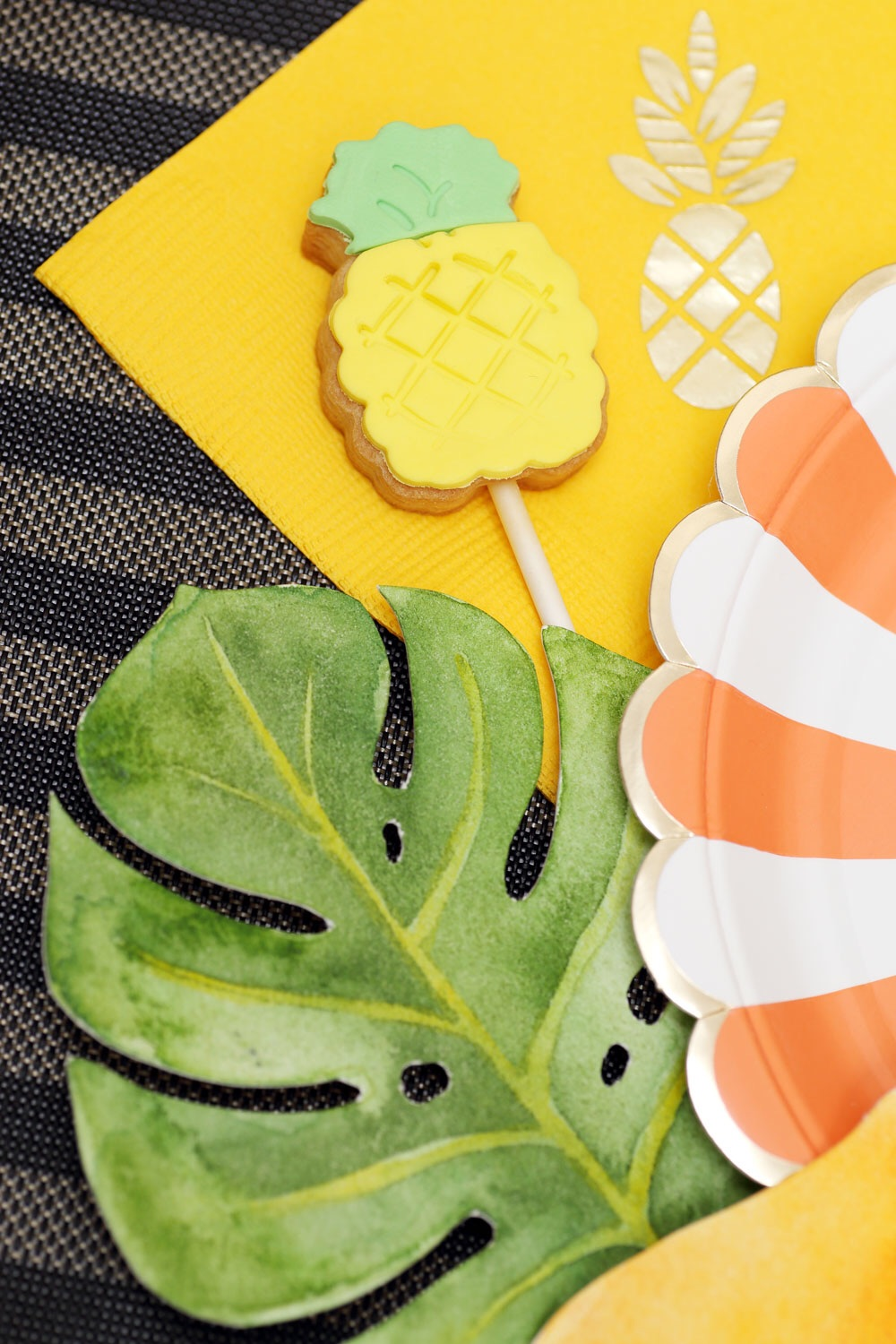 The gold foil stamped napkins are from Love the Occasion and the pineapple cookie pops are from One Sweet Chick. Monstera leaf by ELK Prints.