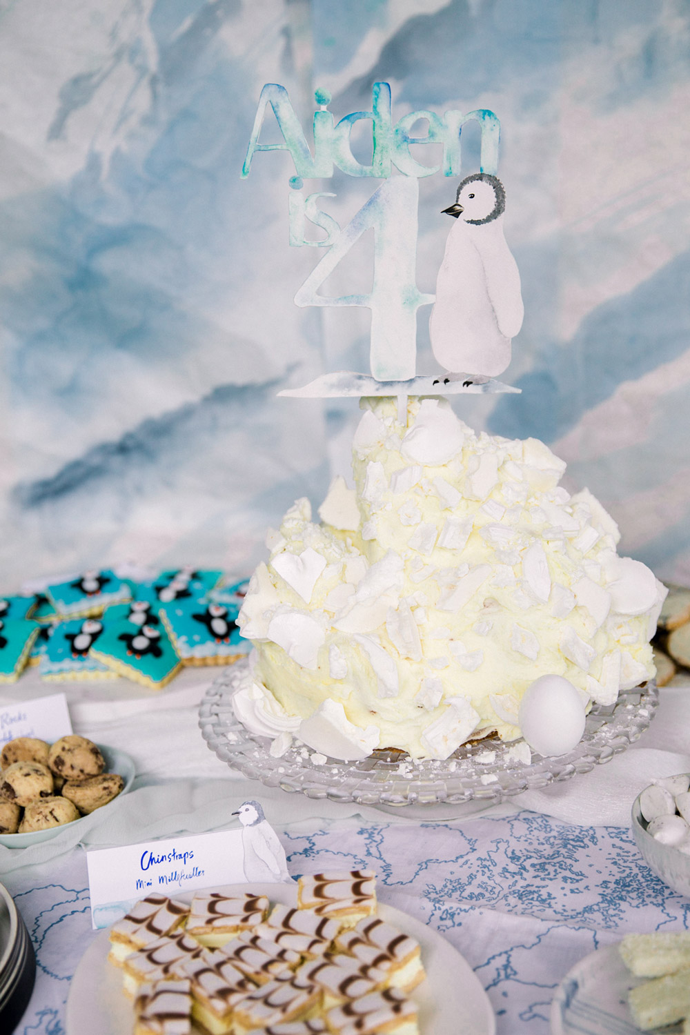 "An ""iceberg"" cake was made for the central birthday cake, shards of meringue embedded in the frosting were used to indicate ice and the custom cake topper represented the penguin."