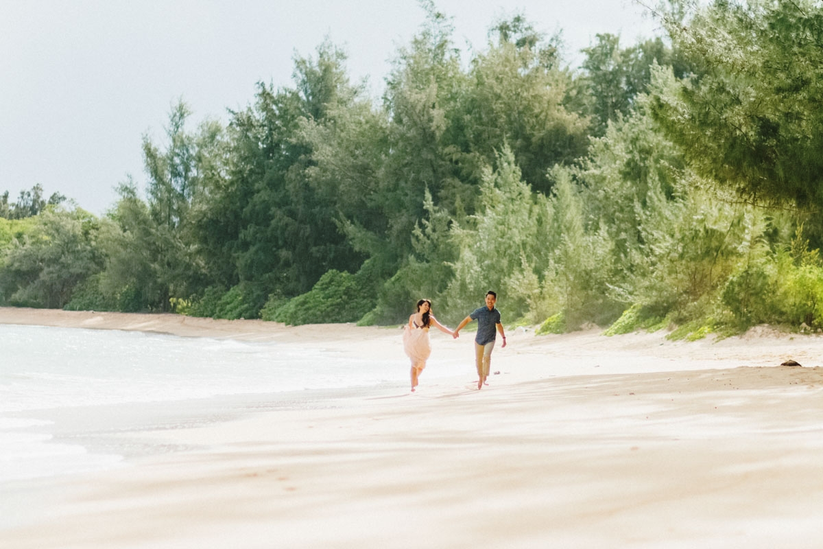 Beach engagagement session couple running in the sand