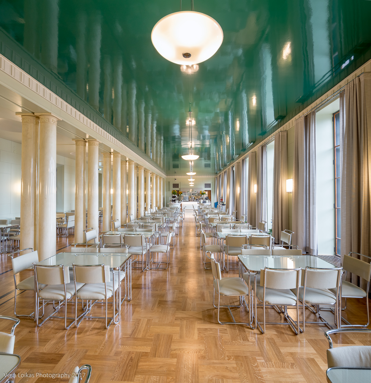 The cafeteria with a mirror-like green ceiling and functionalist furniture. Eduskuntatalon kahvila peilimäisellä vihreällä katolla.