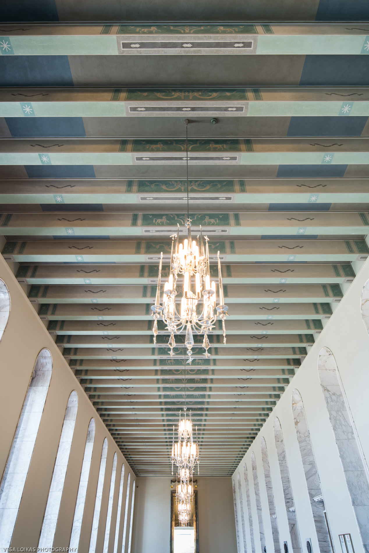 The hall of state (valtiosali) with its decorative ceiling and light fixtures.