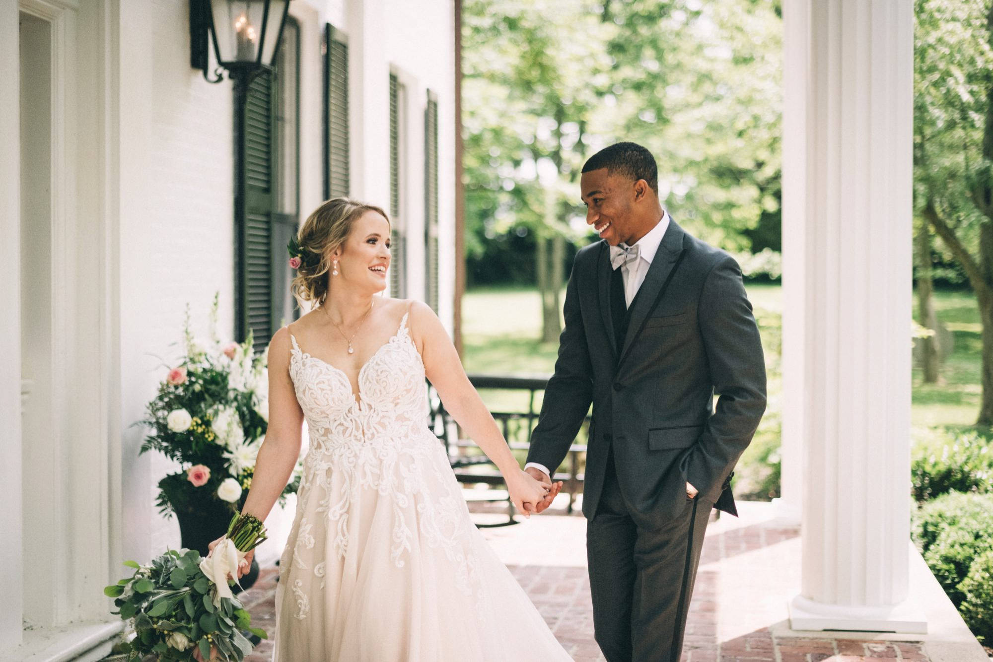 Annastasia and Taylor hold hands. They are on the porch of Ashford Acres Inn. You can see a white column, black shutters,  white walls and green trees in the background. her bouquet is full of blush and ivory flowers and a variety of greenery. Her dress has lace and sweet hear neckline. He is wearing a gray suit.