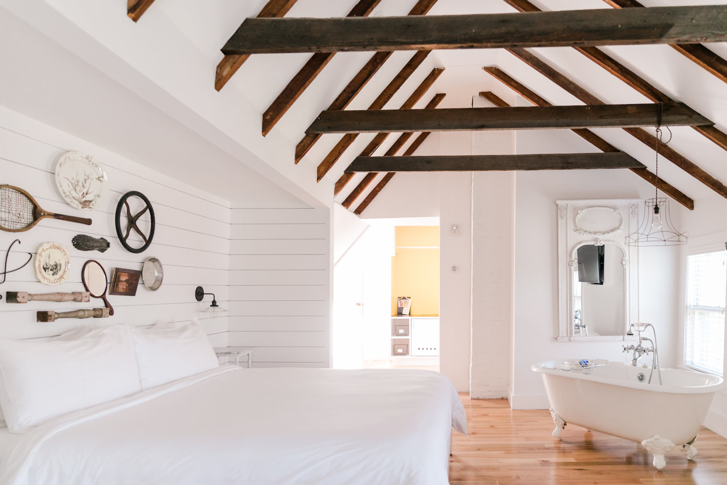 Loft style hotel room with white bed, gallery wall