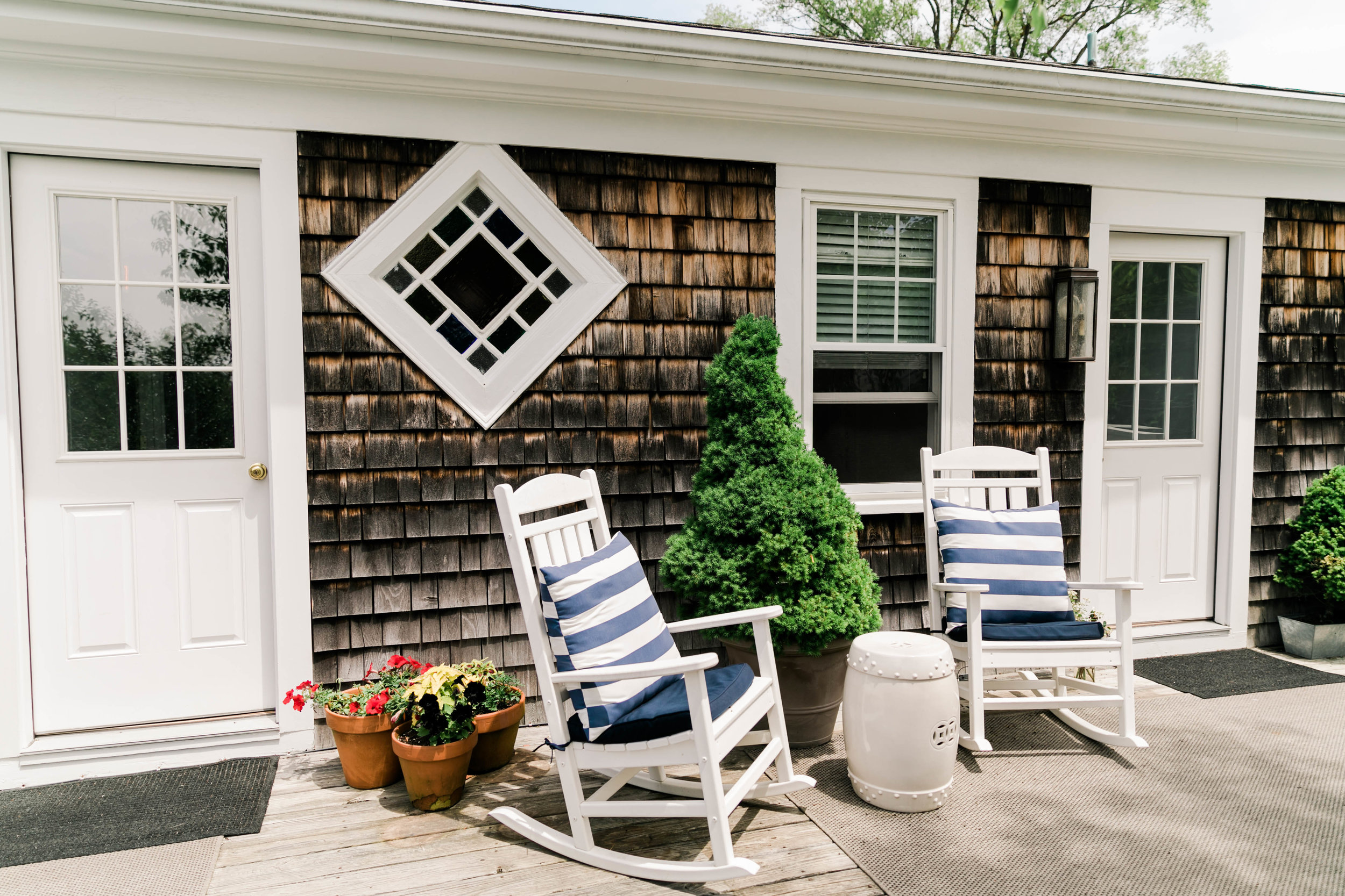 Cape Cod Style house exterior with rocking chairs