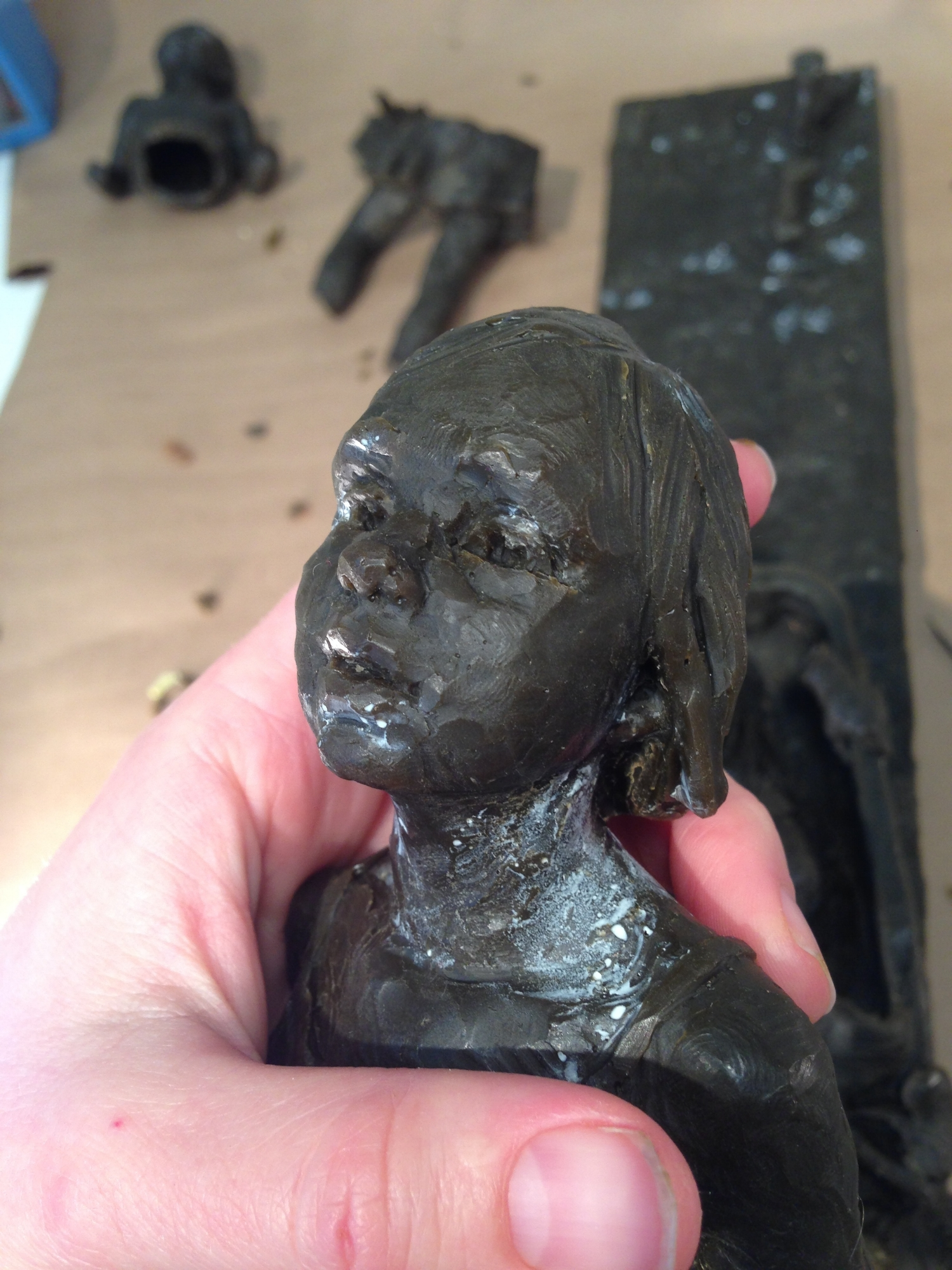 Mardie holding the wax cast of the girl while cleaning up imperfections in the wax as part of the process in bronze casting.